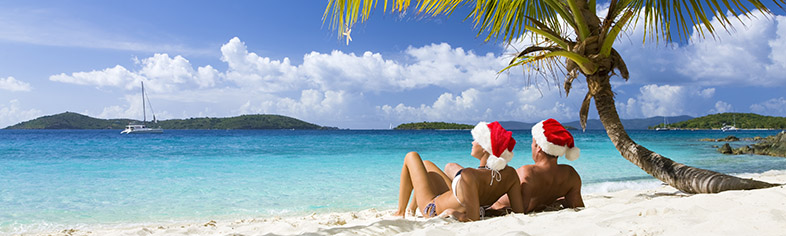 Couple with santa hats on Caribbean beach