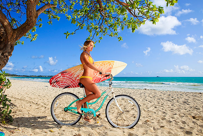 Woman riding bike on Hawaii beach