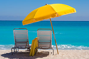 Beach chairs under the shade of an umbrella