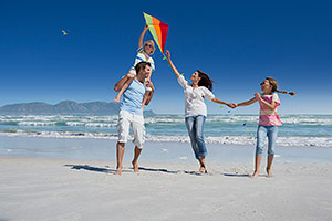 Family flying kite on beach